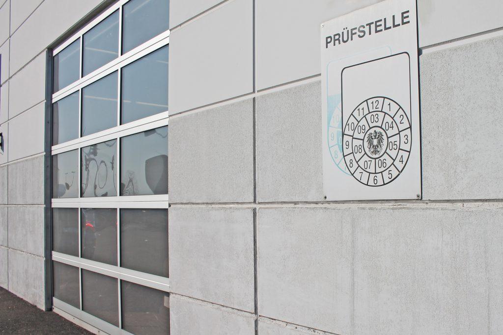 """Schild """"Pickerlüberprüfung"""" an Hausmauer"""